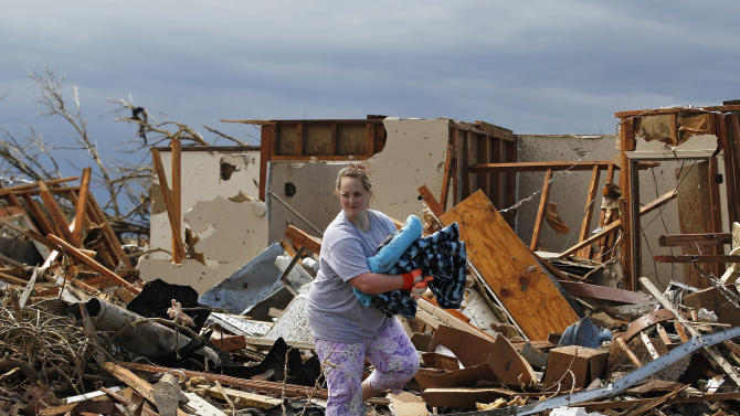 Kandi Scott salvages items from the rubble of her home, which she shared with her mother, until it was destroyed Monday when a tornado moved through Moore, Okla., Tuesday, May 21, 2013. The huge tornado roared through the Oklahoma City suburb, flattening entire neighborhoods and destroying an elementary school with a direct blow as children and teachers huddled against winds.(AP Photo/Brennan Linsley)