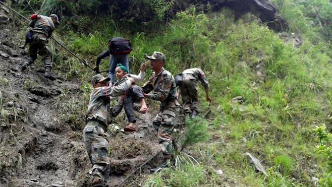 In this Tuesday June 18, 2013 photo released by Indian army, Indian army soldiers help a child to climb down from a mountain, in Uttarkashi, in northern Indian state of Uttrakhund. India's army and air force have evacuated nearly 12,000 Hindu pilgrims stranded in a mountainous area after torrential monsoon rains and landslides caused death and destruction in northern India. At least 69 people have died and 63,000 people remain stranded. (AP Photo/Indian Army)