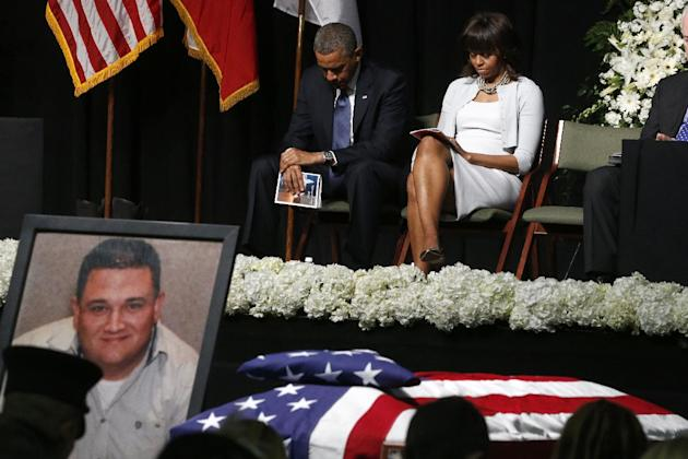 President Barack Obama and first lady Michelle Obama bow their heads behind a photo of volunteer firefighter Capt. Cyrus Adam Reed, who was killed, as they attend the memorial for victims of the ferti