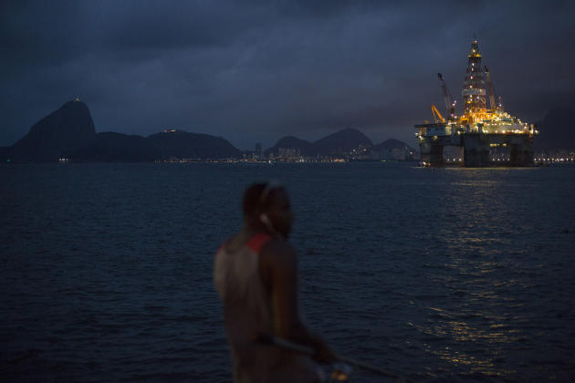 In this April 21, 2015 photo, a man fishes near a floating oil platform in Guanabara Bay in Niteroi, Brazil. Five years ago when Brazil's economy was booming, foreign workers were arriving in droves,