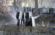 Riot police officers and a woman take cover behind shields during clashes between anti-government protesters with police in Kiev, February 18, 2014. REUTERS/Maks Levin