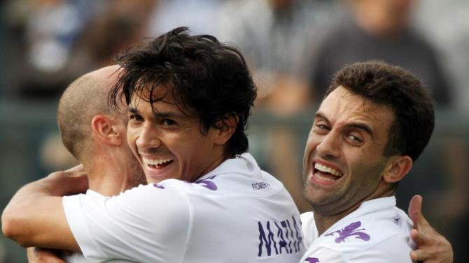 Fiorentina's Vecino Falero Matias, of Uruguay, center, is hugged by his teammates Giuseppe Rossi, right, and Iglesias Borja Valero, of Spain, after scoring during a Serie A soccer match against Atalanta in Bergamo, Italy, Sunday, Sept. 22, 2013