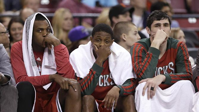 Milwaukee Bucks' Khris Middleton, left, Brandon Knight, Center, and Ersan Ilyasova, of Turkey, watch the closing moments of the Bucks 124-107 loss to the Sacramento Kings in a NBA basketball game in Sacramento, Calif., Sunday, March 23, 2014