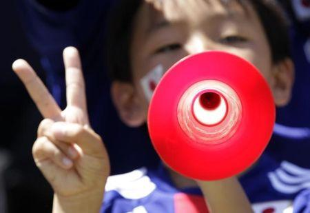 A young Japan soccer supporter plays the vuvuzela before the international friendly soccer match between Japan and Ivory Coast in Sion