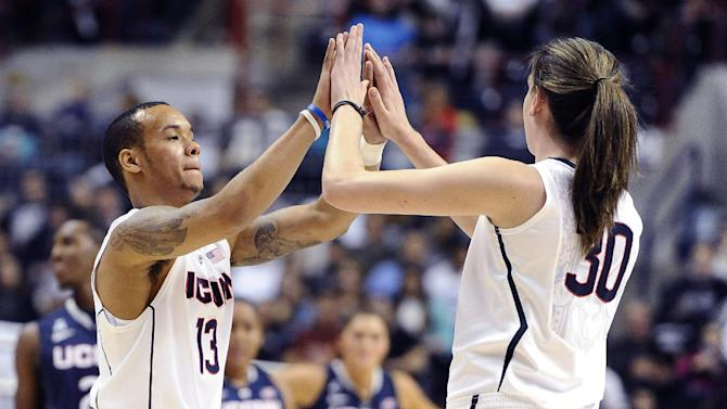 Connecticut's Shabazz Napier, left, high-fives teammate Breanna Stewart during an inter-squad scrimmage at the men's and women's basketball teams' First Night event in Friday, Oct. 18, 2013, in Storrs, Conn