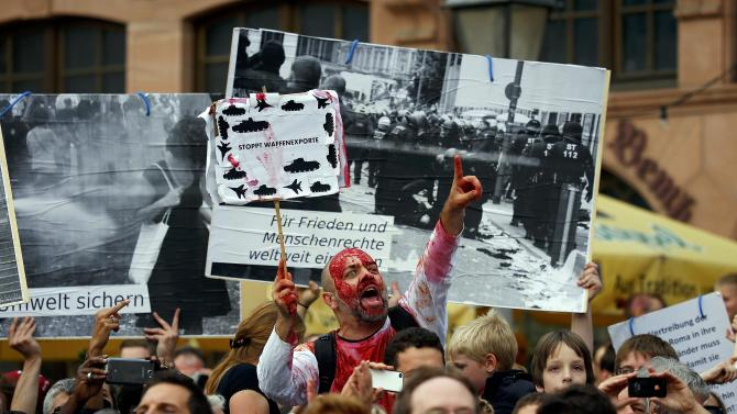 """A protestor holds a poster with the slogan """"stop arms exports"""" as he demonstrates against a CDU election campaign rally at Roemerberg square in Frankfurt"""