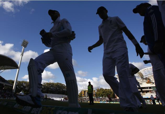 England's captain Cook walks off the ground with wicketkeeper Prior and the rest of the team at the end of the first day's play in the second Ashes cricket test against Australia at the Adelai