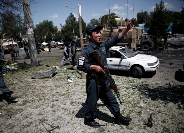 An Afghan policeman reacts at the site of a suicide bomb attack in Kabul, Afghanistan
