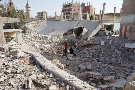 Residents inspect damage in Tafas town in Daraa