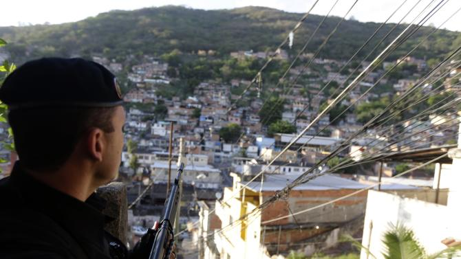 A police officer patrols at the Arvore Seca slum in the Lins slum complex during an operation in Rio de Janeiro