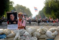 A Thai anti-government protestor holds a poster of King Bhumibol Adulyadej during a stand-off with police near Government House in Bangkok, on February 18, 2014