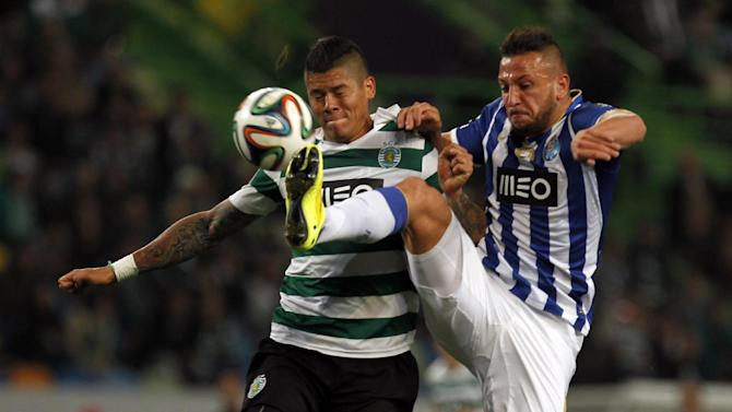 Porto's Nabil Ghilas, from Algeria, tussles for the ball with Sporting's Marcos Rojo, left, from Argentina, during the Portuguese league soccer match between Sporting and Porto at Sporting's Alvalade stadium, in Lisbon, Sunday, March 16, 2014. Sporting won 1-0