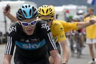 A fan runs behind overall leader's yellow jersey, British Bradley Wiggins, and second placed in the overall standings, Great Britain's Christopher Froome (L) as they ride in the seventeenth stage of the 2012 Tour de France cycling race starting in Bagneres-de-Luchon and finishing in the ski resort of Peyragudes, southern France