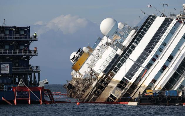 """Salvage crew looks at the capsized cruise liner Costa Concordia during the """"parbuckling"""" operation, outside Giglio harbour"""
