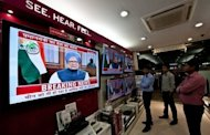 People watch a televised speech by Indian Premier Manmohan Singh in New Delhi. While political opponents accused Singh of selling out the country to foreign interests, the media lauded him for addressing the difficulties facing Asia's third-largest economy.