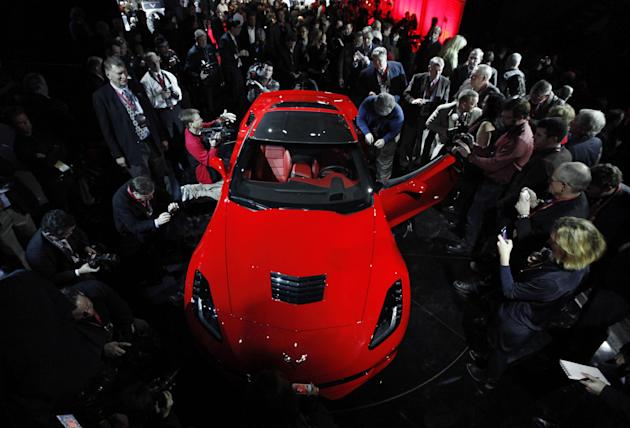 Journalists surround General Motors new 2014 Chevrolet Corvette Stingray, Sunday, Jan. 13, 2013, the night before press days at the North American International Auto Show in Detroit. When 1,000 GM eng