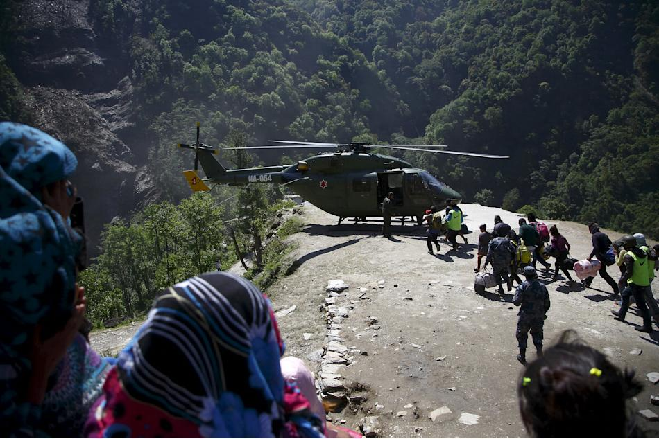 Earthquake victims run towards a helicopter to get airlifted to Kathmandu after last week's earthquake at Sindhupalchok District
