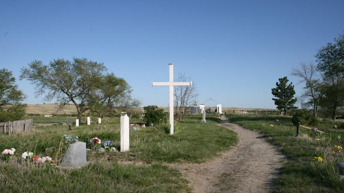 This May 13, 2012, photo shows the Wounded Knee Cemetery in Wounded Knee, S.D. The site, located on the Pine Ridge Indian Reservation, which is home to the Oglala Sioux Tribe, is where more than 250 Lakota men, women and children were killed by the 7th Cavalry in 1890. Some tribal members believe the area should be developed into a tourist attraction with a museum. Others, however, are adamantly opposed to development at the site, saying it would be disrespectful since it's a mass gravesite. (AP Photo/Kristi Eaton)