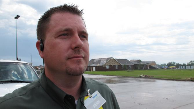 In this Thursday, May 23, 2013 photo, Wal-Mart manager Adam Stutzman stands behind his store in Moore, Okla. More than five dozen workers, customers and passersby took shelter in the store's meat room from Monday's tornado, which collapsed the church in the background. (AP Photo/Allen Breed)