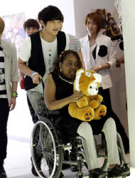 Donika Sterling from New York, in a wheelchair, gets help from Minho, a member of SHINee, on her arrival for meeting with the South Korean pop group in Seoul, South Korea, Wednesday, June 20, 2012. The 15 year-old American K-pop fan, who is suffering a disease that gradually causes loss of muscle tissue and slows down parts of the body, met and sang with the boy band she idolizes. (AP Photo/Lee Jin-man)