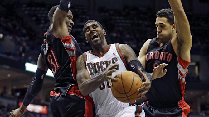 Milwaukee Bucks' O.J. Mayo tries to drive between Toronto Raptors' Terrence Ross (31) and Landry Fields during the second half of an NBA basketball game Saturday, Nov. 2, 2013, in Milwaukee. The Raptors won 97-90