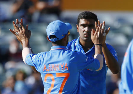 India's bowler Ravichandran Ashwin celebrates with team mate Ajinkya Rahane after bowling out UAE's Mohammed Naveed during their Cricket World Cup match in Perth