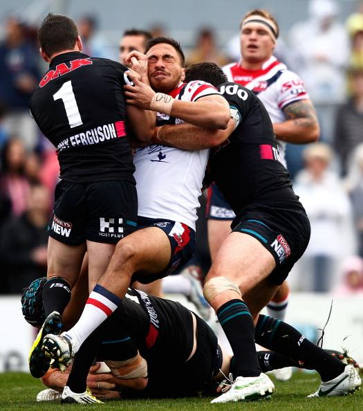 Adam Henry (C) of the Roosters is tackled by the Panthers defence during the round 20 NRL match between the Penrith Panthers and the Sydney Roosters at Centrebet Stadium on July 22, 2012 in Sydney, Australia. (Photo by Brendon Thorne/Getty Images)