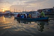 Indonesian Muslim devotees arrive on a boat to attend the morning prayer to celebrate the Eid al-Fitr festival at the historic Sunda Kelapa port district of Jakarta on July 28, 2014