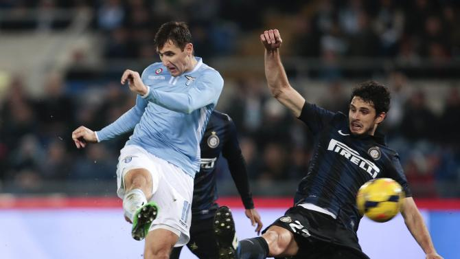 Lazio's Klose shoots to score as he is challenged by Inter Milan's Ranocchia during their Italian Serie A soccer match at the Olympic stadium in Rome