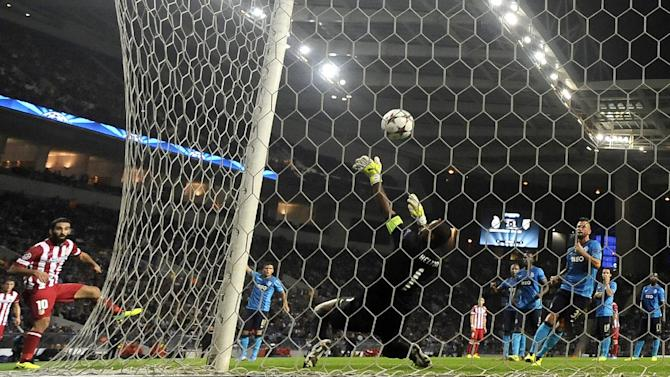 Atletico's Arda Turan, left, scores his side's second goal past Porto's goalkeeper Helton during the Champions League group G soccer match between FC Porto and Atletico de Madrid Tuesday, Oct. 1, 2013, at the Dragao stadium in Porto, northern Portugal. Atletico won 1-0