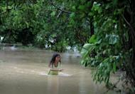 A girl wades through floodwaters after a river overflowed following heavy rains caused by Tropical Storm Saola in Manila on Monday. Tens of thousands battled neck-deep floods in the Philippines Tuesday as Typhoon Saola continued to bring heavy rains, with the death toll from the storm rising to eight, officials said