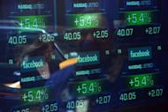 Screens display the start of trading in Facebook shares at the NASDAQ stock exchange on Times Square in New York, on May 18, 2012. Facebook is increasing its revenue from mobile with more users now accessing the social network via smartphones and tablets than from personal computers, but Wall Street remains unimpressed