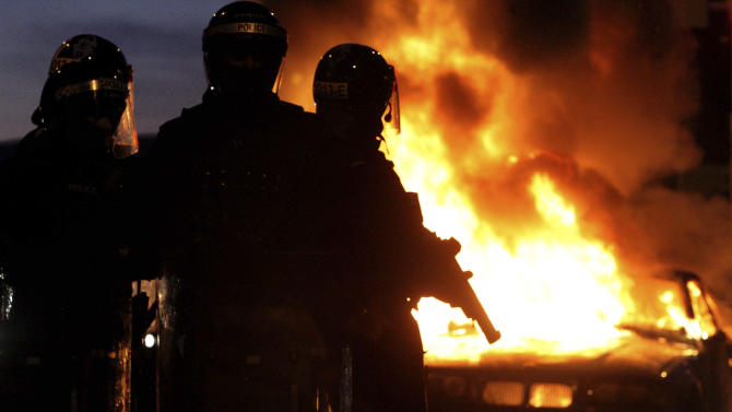 Riot police stand next to a burned out car after Loyalist protesters attacked police lines, in east BelfastNorthern Ireland, Saturday Jan. 12, 2013. Police used water cannons as four officers were injured during sectarian clashes between loyalists and republicans in east Belfast, Saturday. Trouble flared after a city centre demonstration against the council's decision to limit the number of days the Union flag is flown from City Hall (AP Photo/Paul Faith/PA) UNITED KINGDOM OUT