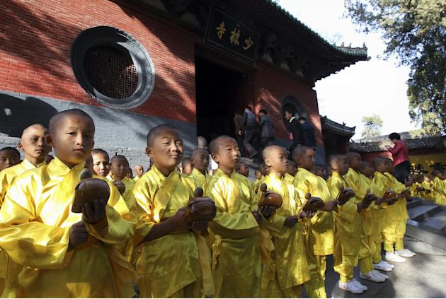 In this Oct. 22, 2012 photo, visitors walk past as young monks offer prayers outside the Shaolin Temple in Dengfeng city in central China's Henan province. The temple which is historically known f