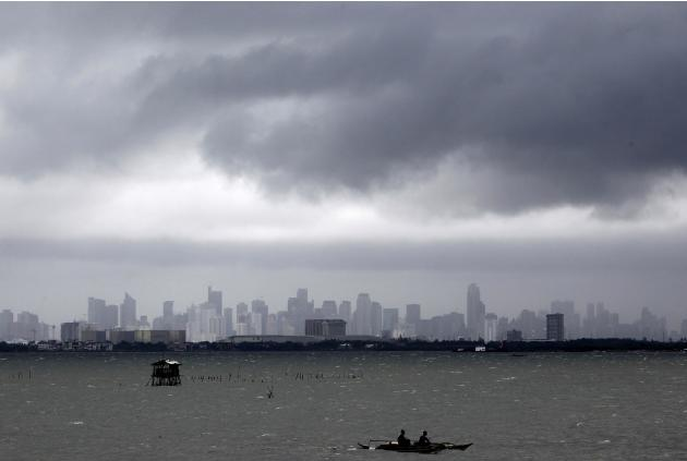 Fishermen ride on their boat as dark clouds loom over the city brought by Typhoon Usagi in Manila
