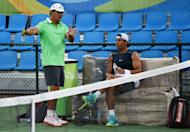 Rafael Nadal of Spain (R) listening to his coach and uncle Toni Nadal during a tennis practice session at the Olympic park in Rio de Janeiro ahead of the 2016 Rio Olympic Games