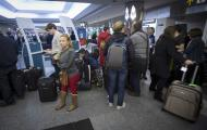 People line up for information about their flights at La Guardia airport in New York January 6, 2014. Winter and accompanying storms are a major issue for U.S. airlines in the first quarter. Airlines typically will proactively cancel flights during a major storm to minimize disruptions. REUTERS/Carlo Allegri (UNITED STATES - Tags: TRANSPORT ENVIRONMENT)