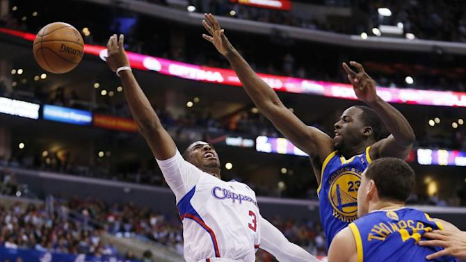 Los Angeles Clippers' Chris Paul, left, loses the ball as he attempts a shot while Golden State Warriors' Draymond Green, right, defends and Warriors' Klay Thompson watches during the first half of an NBA basketball game in Los Angeles, Wednesday, March 12, 2014