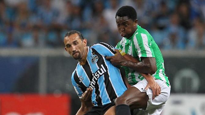 Hernan Barcos of Brazil's Gremio, left, fights for the ball with Oscar Murillo of Colombia's Atletico Nacional during a Copa Libertadores soccer game in Porto Alegre, Brazil, Tuesday, Feb.25, 2014