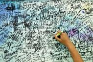 A man writes messages and well-wishes for family members of passengers onboard the missing Malaysia Airlines Flight MH370 inside a shopping mall in Putrajaya, March 20, 2014. REUTERS/Samsul Said