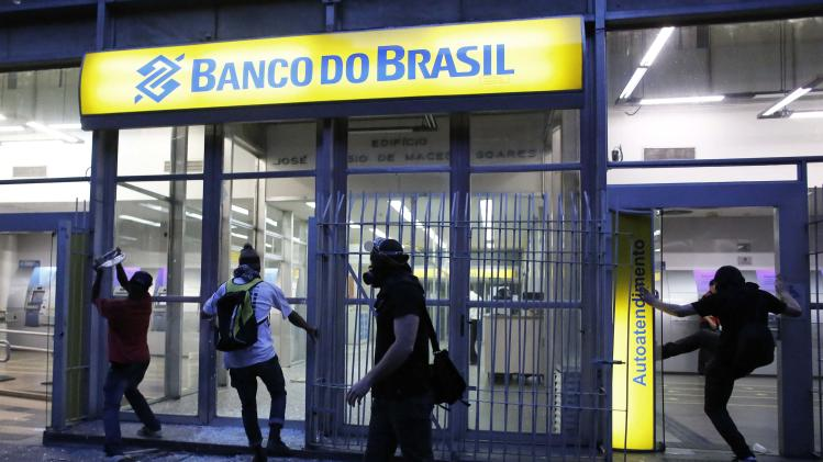 Demonstrators attack a Brasil bank branch during a protest against the 2014 World Cup, in Sao Paulo