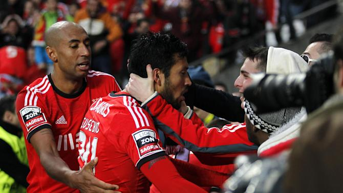 Benfica's Ezequiel Garay, centre, from Argentina, celebrates with teammate Luisao, left, from Brazil, and supporters after scoring their side's second goal against Porto during the Portuguese league soccer match between Benfica and Porto at Benfica's Luz stadium in Lisbon, Sunday, Jan. 12, 2014