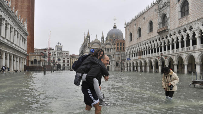 People cross flooded St. Mark's Square in Venice, Italy, Thursday, Nov. 1, 2012. High tides have flooded Venice, leading Venetians and tourists to don high boots and use wooden walkways to cross St. Mark's Square and other areas under water. Flooding is common this time of year and Thursday's level that reached a peak of 55 inches (140 centimeters) was below the 63 inches (160 centimeters) recorded four years ago in the worst flooding in decades. (AP Photo/Luigi Costantini)