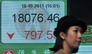 A woman walks past a display board showing the Hang Seng stock market index in Hong Kong, 2011. Asian markets fell and the euro sat near multi-year lows amid growing fears that Spain will need a full bailout, while tech shares were hit by Apple's disappointing earnings report