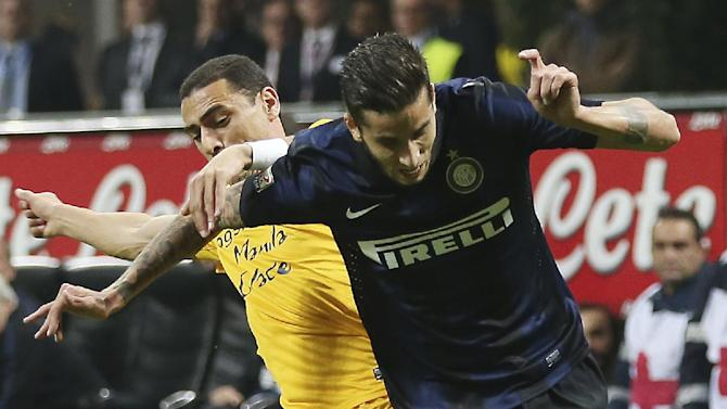 Inter Milan midfielder Ricardo Alvarez, right, of Argentina, challenges for the ball with Hellas Verona Brazilian midfielder Romulo Souza during the Serie A soccer match between Inter Milan and Hellas Verona at the San Siro stadium in Milan, Italy, Saturday, Oct. 26, 2013