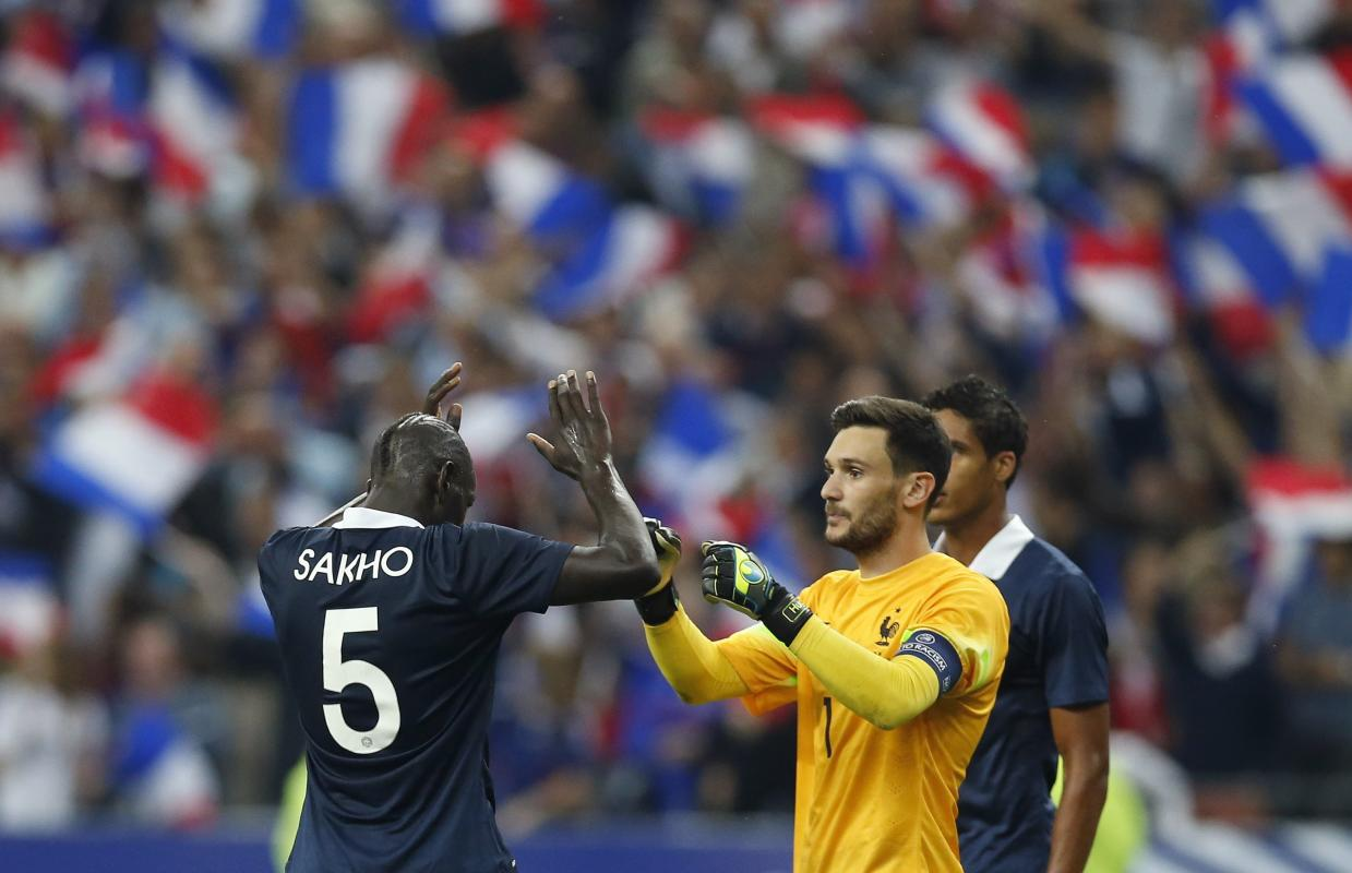 France's captain Lloris celebrates with team mate Sakho after defeating Spain during their international friendly soccer match at the Stade de...