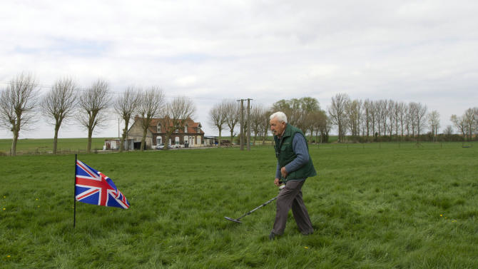In this photo taken on Monday, April 22, 2013, amateur archeologist and historian Moise Dilly runs a metal detector over the area in which he located the bodies of two British World War I soldiers in 2009 in a field in Bullecourt, France. Almost 100 years after they were killed in action, Lt. John Harold Pritchard and Pvt. Christopher Douglas Elphick will be re-interred with full military honors in the H.A.C Cemetery at Ecoust-St. Mein, France, on Tuesday, April 23, 2013. (AP Photo/Virginia Mayo)