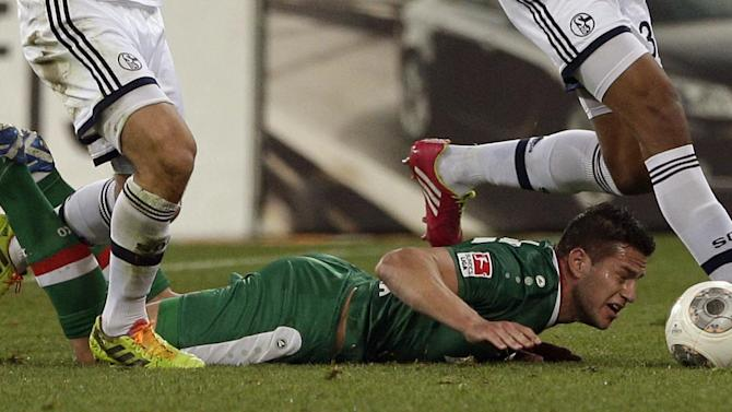Augsburg's Raul Bobadilla of Argentina lies on the ground during the German first division Bundesliga soccer match between FC Augsburg and FC Schalke 04, in Augsburg, southern Germany, Friday, March 14, 2014