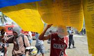 Residents look at lists displaying names of missing people in New Bataan, Philippines, on December 12, 2012. The death toll from a typhoon that devastated the southern Philippines earlier this month has topped 1,000 as hundreds more remain missing, the government said on Sunday