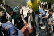 A wounded Syrian man is lifted off the back of a pick-up truck following shelling by Syrian government forces on al-Qusayr, close to the restive city of Homs